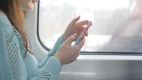 Ragazza che viaggia in un treno e che per mezzo del telefono cellulare La bella donna invia un messaggio dallo smartphone attraen Fotografie Stock