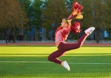 Ragazza Cheerleading su un salto di addestramento di mattina all'alba su un campo all'aperto Sport, salute, forma fisica fotografie stock