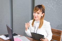Ragazza cinese asiatica attraente che si siede sul banco di parco che lavora alla compressa del computer portatile casuale fotografie stock libere da diritti