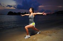Ragazza cinese asiatica che fa allungamento sulla spiaggia Fotografie Stock Libere da Diritti