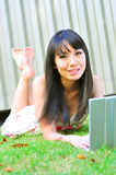 Ragazza cinese asiatica che per mezzo del computer portatile Immagini Stock