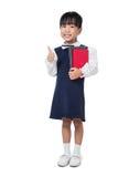 Ragazza cinese asiatica della scuola primaria in uniforme che mostra i pollici su Fotografie Stock Libere da Diritti