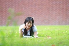Ragazza cinese asiatica rilassata che si trova sul prato inglese Fotografie Stock Libere da Diritti
