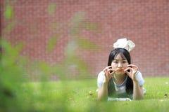 Ragazza cinese asiatica rilassata che si trova sul prato inglese Fotografia Stock Libera da Diritti