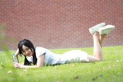 Ragazza cinese asiatica rilassata che si trova sul prato inglese Fotografie Stock