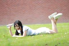 Ragazza cinese asiatica rilassata che si trova sul prato inglese Fotografia Stock