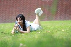Ragazza cinese asiatica rilassata che si trova sul prato inglese Immagini Stock