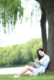 Ragazza cinese che legge un libro sotto l'albero La bella giovane donna bionda con il libro si siede sull'erba Fotografia Stock