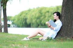 Ragazza cinese che legge un libro sotto l'albero La bella giovane donna bionda con il libro si siede sull'erba Fotografie Stock