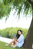 Ragazza cinese che legge un libro sotto l'albero La bella giovane donna bionda con il libro si siede sull'erba Immagini Stock