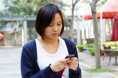 Ragazza cinese che sta concentrandosi sul telefono Immagini Stock