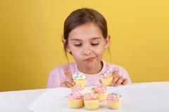 Ragazza circa per mangiare un bigné Fotografie Stock