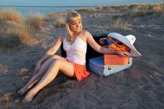 Ragazza con bagaglio sulla spiaggia Fotografia Stock