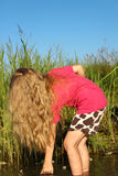 Ragazza con bei capelli dorati lunghi sulla riva del lago fotografie stock libere da diritti