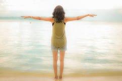 Ragazza con a braccia aperte fare gesto di volo su una spiaggia Immagini Stock