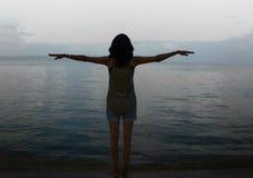 Ragazza con a braccia aperte fare gesto di volo su una spiaggia Immagine Stock