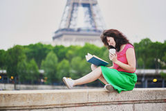 Ragazza con caffè da andare leggere un libro vicino alla torre Eiffel Immagine Stock