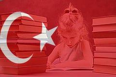 Ragazza con capelli bianchi vuole imparare turco dietro la sua bandiera sulla tavola un mucchio dei libri fotografia stock