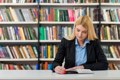Ragazza con capelli biondi che si siedono ad uno scrittorio nei wi delle biblioteche Fotografia Stock Libera da Diritti