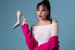 Ragazza con capelli neri che indossano rivestimento rosa e la scarpa bianca del tacco alto della tenuta della blusa a disposizion fotografia stock libera da diritti
