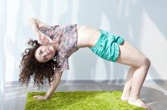 Ragazza con capelli ondulati che fanno yoga di mattina nella stanza Fotografia Stock Libera da Diritti