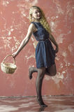 Ragazza con capelli ricci biondi in un vestito lungo con il wiiiiiiiiiiith dei pois un canestro Immagini Stock Libere da Diritti