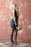 Ragazza con capelli ricci biondi in un vestito lungo con il wiiiiiiiiiiith dei pois un canestro Fotografia Stock Libera da Diritti