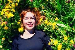 Ragazza con capelli rossi che si trovano sul campo dei denti di leone Fotografie Stock Libere da Diritti