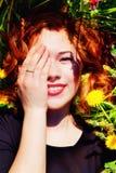 Ragazza con capelli rossi che si trovano sul campo dei denti di leone Immagini Stock