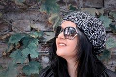 Ragazza con capelli scuri ed il cappello con il muro di mattoni dietro immagini stock libere da diritti