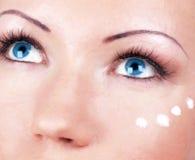 Ragazza con crema per zona degli occhi sul fronte Fotografia Stock
