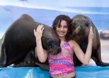 Ragazza con due leoni marini Fotografia Stock Libera da Diritti