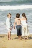 Ragazza con gli amici alla spiaggia Fotografie Stock