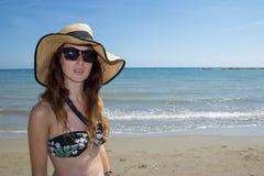 Ragazza con gli occhiali da sole ed il cappello sulla spiaggia Fotografie Stock
