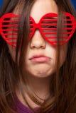 Ragazza con gli occhiali da sole a forma di del cuore Immagine Stock