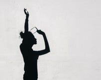 Ragazza con gli occhiali da sole la sua mano verso il cielo intorno sui precedenti bianchi della parete Fotografie Stock Libere da Diritti