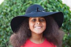 Ragazza con i capelli lunghi di afro e black hat graziosi Fotografia Stock