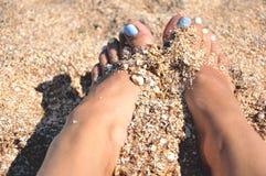 Ragazza con i capelli lunghi sulla spiaggia che gioca con la sabbia e sorridere Immagini Stock Libere da Diritti