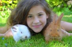 Ragazza con i conigli rossi di California e della Nuova Zelanda Fotografia Stock