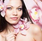 Ragazza con i fiori dell'orchidea in capelli Fotografia Stock