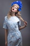 Ragazza con i fiori sulla sua testa in un vestito nello stile russo fotografia stock libera da diritti