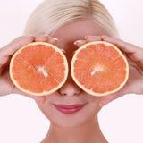 Ragazza con i frutti arancio isolata su fondo bianco, giovane donna bionda sorridente immagini stock