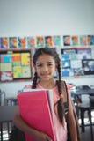 Ragazza con i libri in aula Fotografia Stock Libera da Diritti