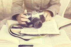 Ragazza con i libri e la vecchia macchina fotografica Immagini Stock