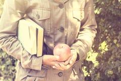 Ragazza con i libri e una mela, effetto d'annata della foto Immagine Stock