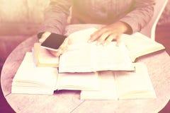 Ragazza con i libri ed il telefono cellulare, effetto d'annata di colore Fotografia Stock