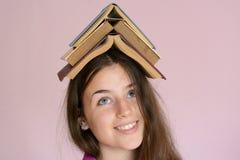 Ragazza con i libri sulla sua testa Immagini Stock Libere da Diritti