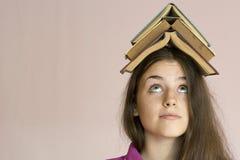 Ragazza con i libri sulla sua testa Fotografie Stock