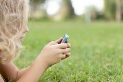 Ragazza con i mobiles che riposano sull'erba immagini stock libere da diritti