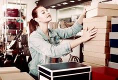 Ragazza con i pacchetti del cartone nel negozio delle borse Immagine Stock Libera da Diritti